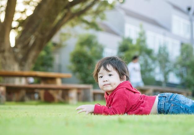 Il bambino asiatico del primo piano ha mentito sul pavimento dell'erba nei precedenti del giardino con la luce del sole