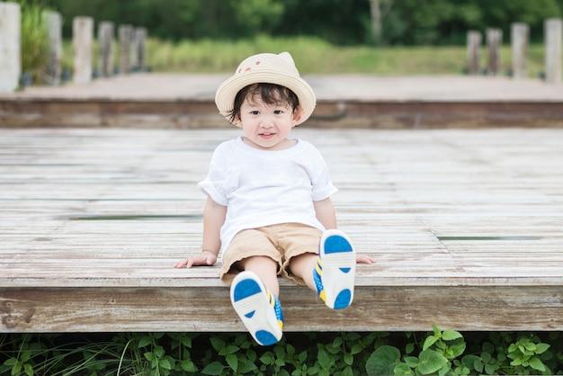 Il bambino asiatico felice del primo piano con il fronte di sorriso si siede alla via di legno nei precedenti del parco