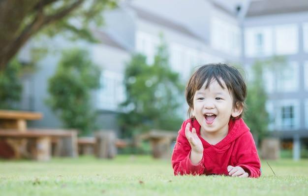 Il bambino asiatico felice del primo piano ha mentito sul pavimento dell'erba nei precedenti del giardino con moto sveglio