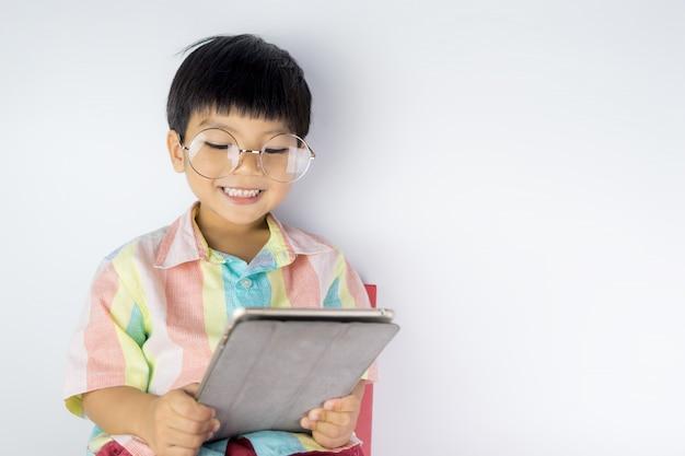 Il bambino asiatico felice sta studiando sulla compressa su fondo bianco