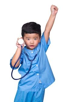 Il bambino asiatico in uniforme medica blu con lo stetoscopio ha isolato il percorso di ritaglio.