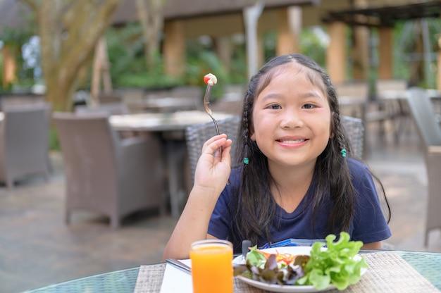 Il bambino asiatico si diverte a mangiare l'insalata vegetariana