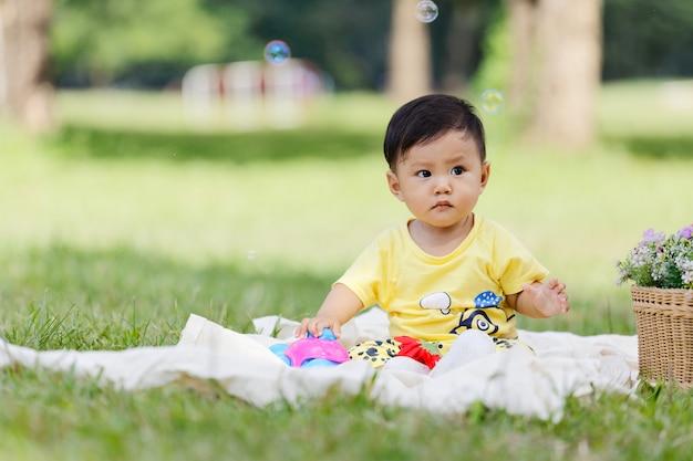 Il bambino asiatico sorridente dei bambini e dei capelli neri del ragazzo si siede su bianco cotone nell'erba verde da solo e giocando giocattolo.