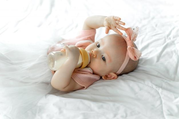 Il bambino beve il latte da una bottiglia su un letto bianco
