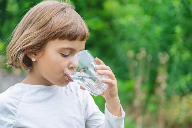 Il bambino beve l'acqua da un bicchiere