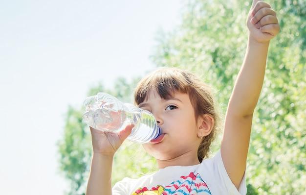 Il bambino beve l'acqua dalla bottiglia. messa a fuoco selettiva.