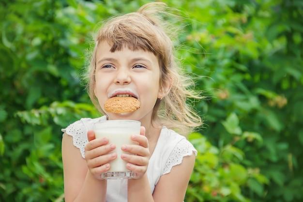 Il bambino beve latte e biscotti. messa a fuoco selettiva