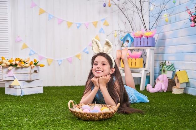 Il bambino celebra la pasqua. divertente bambino felice nelle orecchie di coniglio giocando con le uova di pasqua