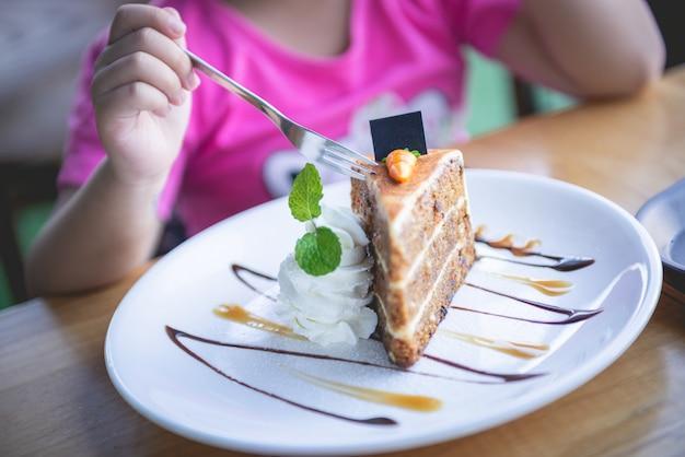 Il bambino che mangia il dolce alle carote ha decorato con la panna montata, il caramello, le foglie di menta su colore bianco del piatto.