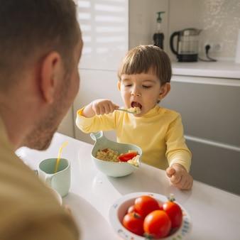 Il bambino che prende i cereali con il cucchiaio e mangia