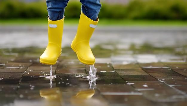 Il bambino che salta nello stagno di acqua al giorno di autunno o di estate