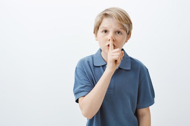 Il bambino chiede all'amico di mantenere il segreto. ritratto di bambino maschio biondo carino serio in maglietta blu dicendo shh mentre si tiene il dito indice sulle labbra piegate, facendo gesto shush