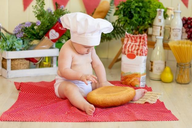 Il bambino con il cappello da cuoco si siede con farina e verdure