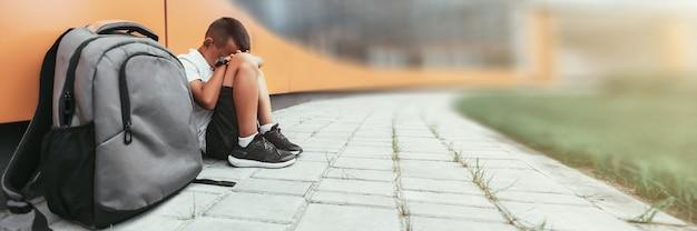 Il bambino con lo zaino in depressione è seduto per terra e non vuole tornare a scuola