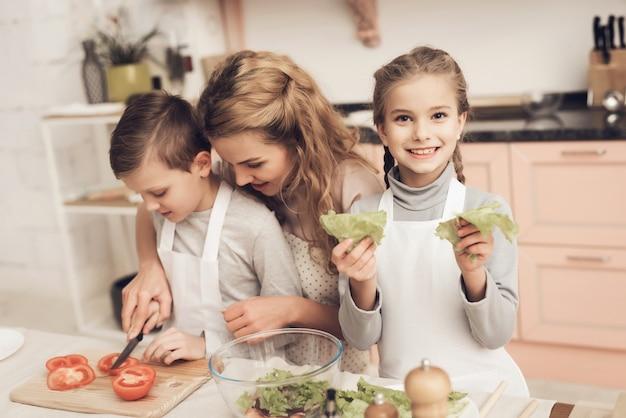 Il bambino dà la foglia della lattuga che cucina l'insalata casalinga.