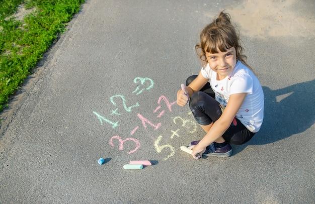 Il bambino decide grugniti sull'asfalto. messa a fuoco selettiva