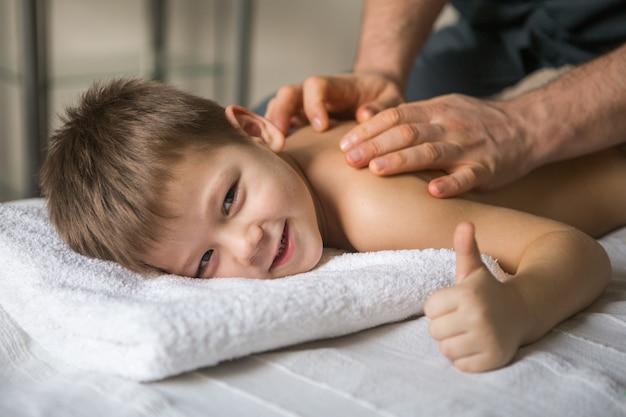 Il bambino del ragazzo si rilassa da un massaggio terapeutico. fisioterapista che lavora con il paziente in clinica alla parte posteriore di un bambino
