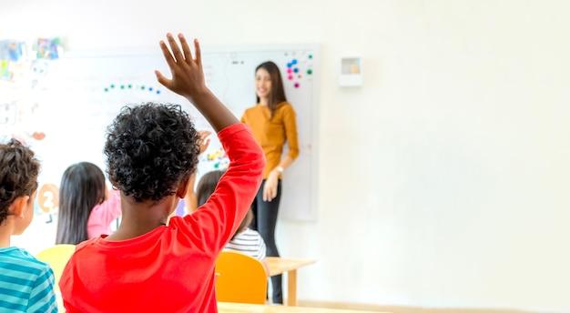 Il bambino di etnia dell'afroamericano passa in su per la domanda di risposta dell'insegnante in aula