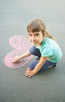 Il bambino dipinge il gesso sul cuore dell'asfalto. messa a fuoco selettiva