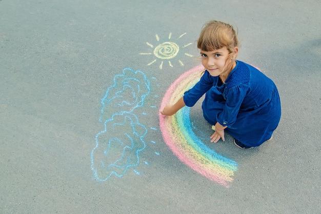 Il bambino disegna con il gesso sul marciapiede