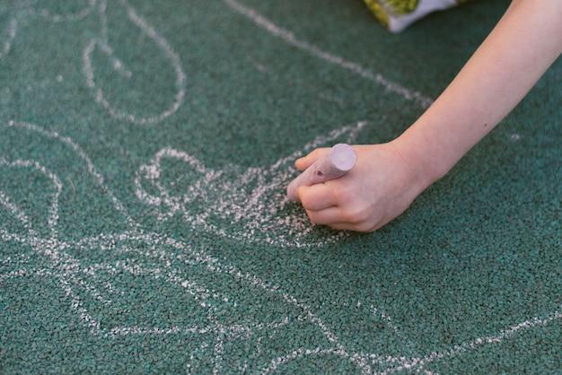 Il bambino disegna con il gesso sulla strada. rivestimento speciale per disegnare nel parco giochi.