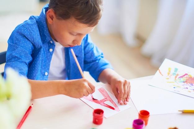 Il bambino disegna con un pennello acquerelli su carta la lettera a