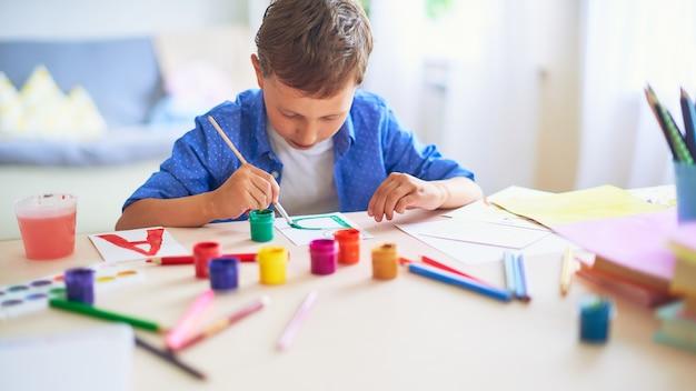 Il bambino disegna con un pennello acquerelli su carta la lettera b