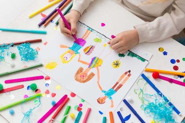 Il bambino disegna i suoi amici con dei pennarelli