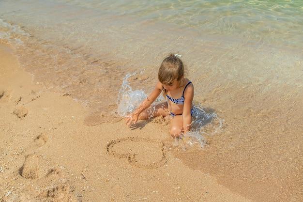 Il bambino disegna nella sabbia sulla spiaggia