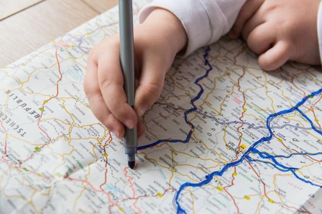 Il bambino disegna sulla mappa con la penna.