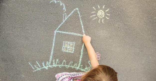 Il bambino disegna una casa di gesso. messa a fuoco selettiva