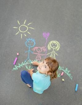 Il bambino disegna una famiglia sul marciapiede con il gesso. messa a fuoco selettiva