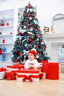 Il bambino disimballa i contenitori di regalo con la decorazione di natale, vestita come santa, le luci del bokeh, concetto di vacanza invernale
