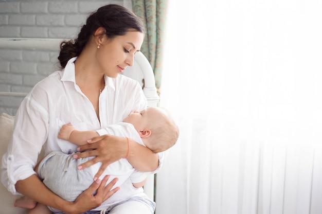 Il bambino dorme sul petto della madre. giovane madre coccole bambino
