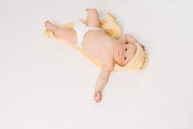 Il bambino è avvolto in un asciugamano morbido giallo dopo il bagno.