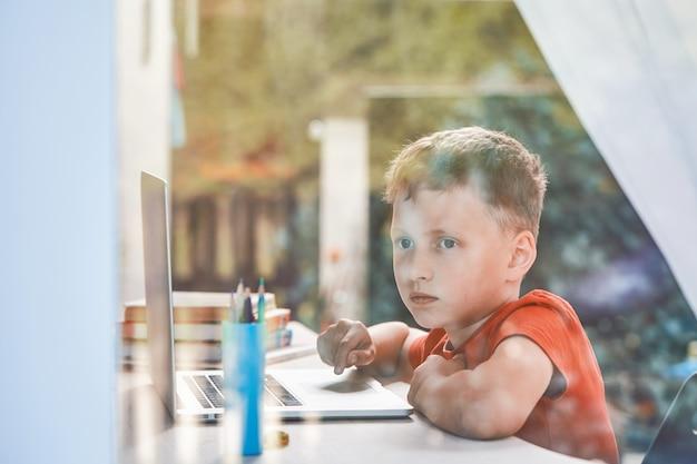 Il bambino è distratto dai suoi studi e guarda fuori dalla finestra