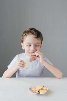 Il bambino è felice di mangiare biscotti fatti in casa con latte
