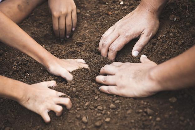 Il bambino e il genitore che scavano il terreno preparano per piantare l'albero insieme