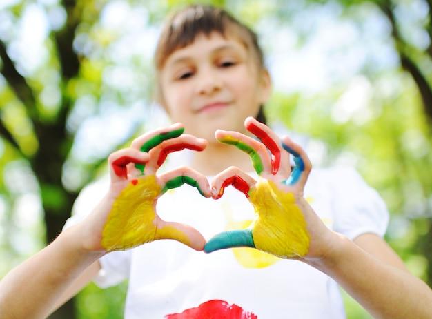 Il bambino è imbrattato di abiti dai colori vivaci che dipinge abiti sorridenti nel parco.