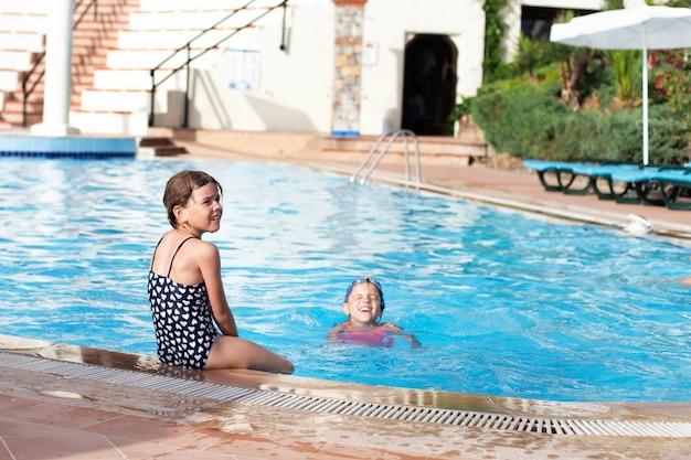 Il bambino è seduto a bordo piscina e i suoi piedi sono nell'acqua