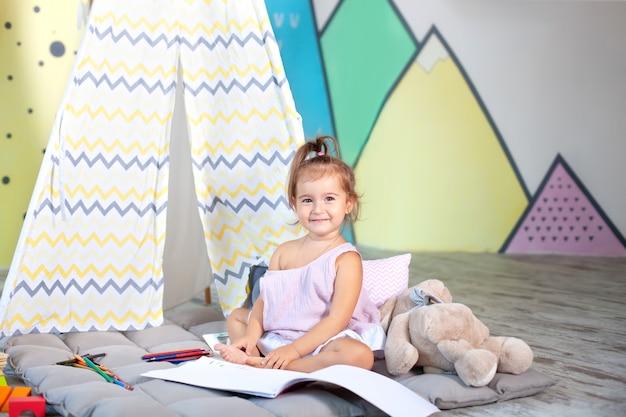 Il bambino fa i compiti. il bambino disegna all'asilo. il bambino in età prescolare impara a scrivere e leggere. ragazzo creativo. la bambina disegna con le matite in un album a casa. concetto di infanzia e sviluppo del bambino
