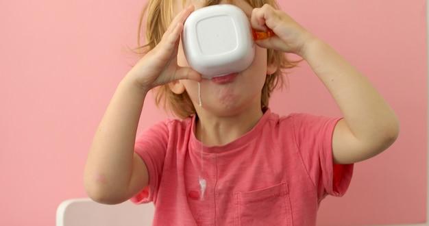 Il bambino felice beve il latte da una tazza