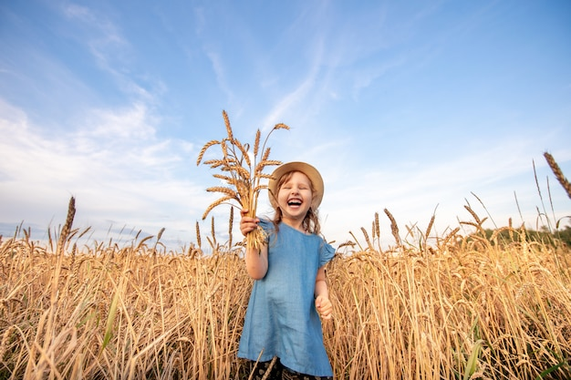 Il bambino felice del ritratto in un campo di grano tira le sue mani verso l'alto