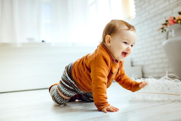 Il bambino felice in maglione arancione gioca con la piuma sul pavimento