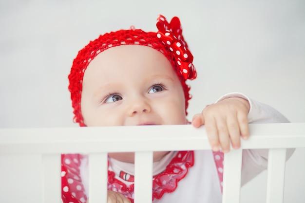 Il bambino felice in protezione rossa osserva in su