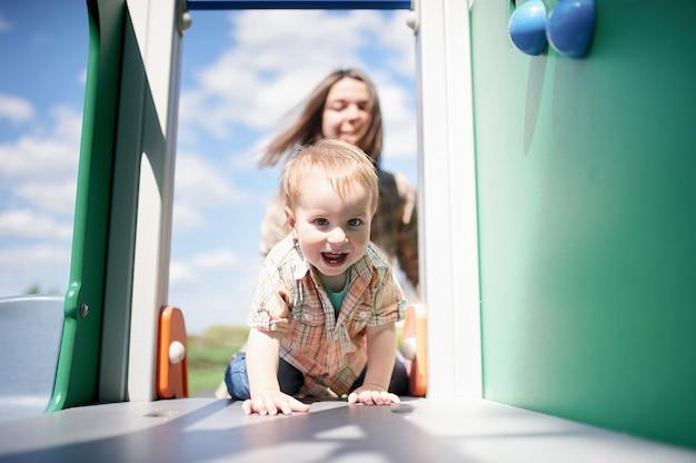 Il bambino felice si arrampica sulla diapositiva nel parco giochi