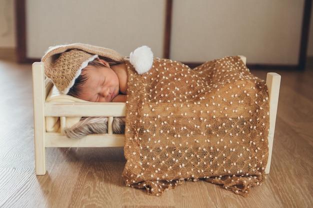 Il bambino giace su un letto di legno sotto una coperta. ritratto di un bambino piccolo in un cappello caldo con un pompon.