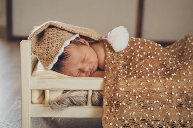 Il bambino giace su un letto di legno sotto una coperta.