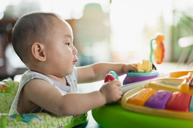 Il bambino gioca con una bambola di plastica colorata