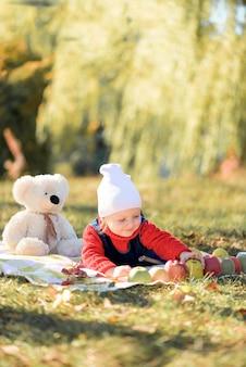Il bambino gioca nella foresta d'autunno con mele e matite. tema autunnale